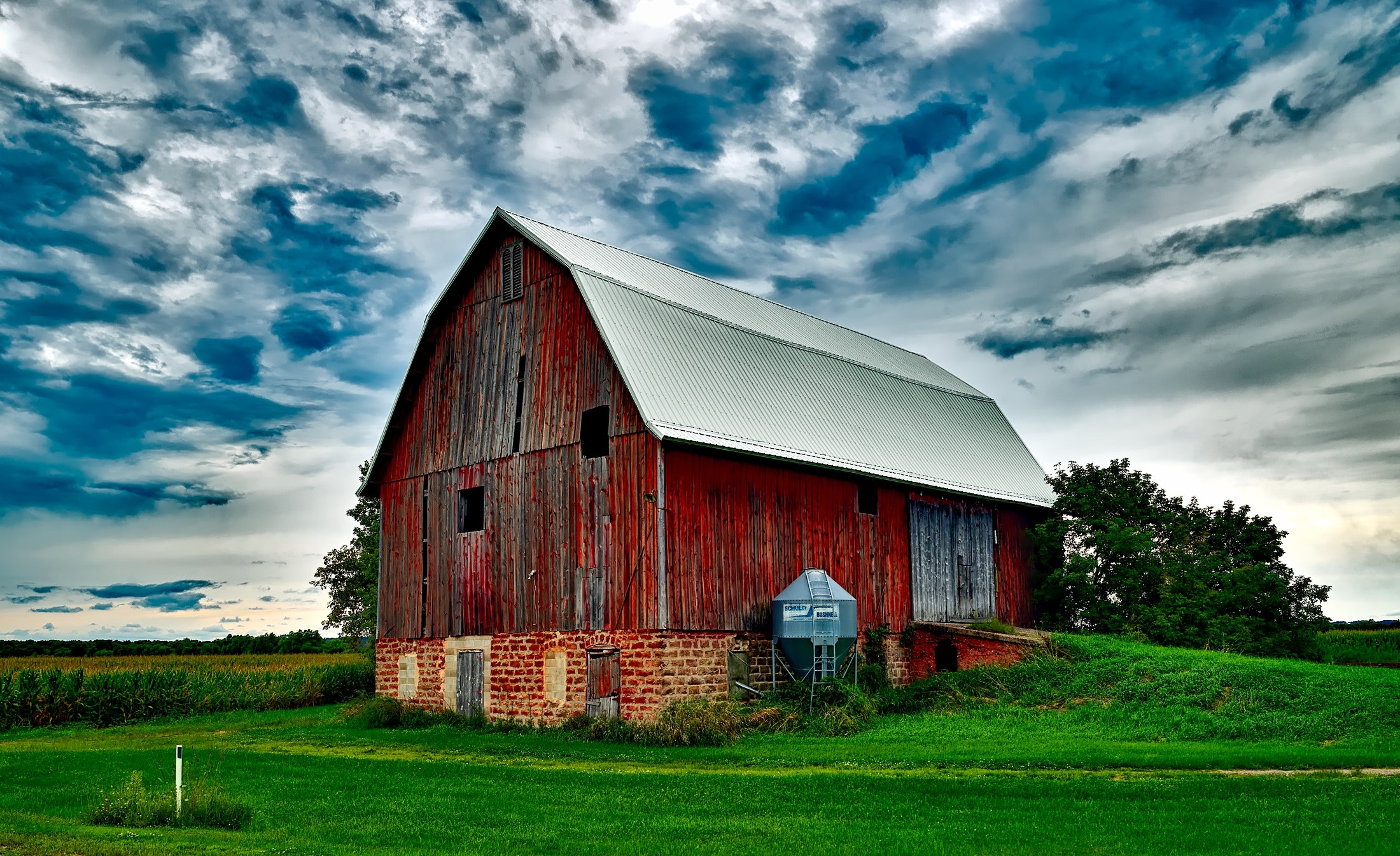 A Barn in a field in front of a cloudy sky.